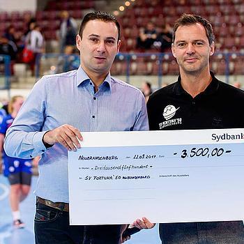 Benny Marlow Standortleiter JACOB CEMENT BAUSTOFFE überreicht einen Scheck im Wert von 3.500 € an den Trainer von SV Fortuna '50 Neubrandenburg