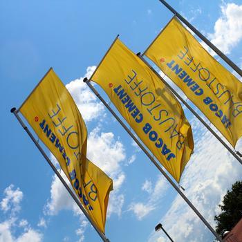 Drei wehende Flaggen vor blauem Himmel mit dem JACOB-CEMENT-BAUSTOFFE-Logo